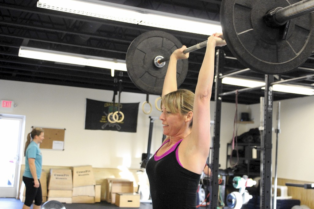 Lisa pressing overhead during the 1100 group WOD.