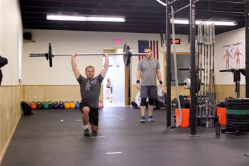 Curtis overhead lunges during the 1700 group WOD.