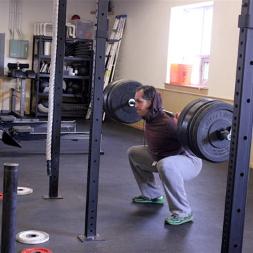 Anthony back squatting during the 1200 group WOD.