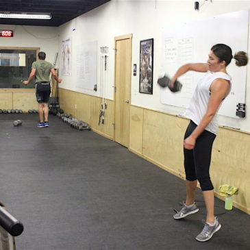 Steph single arm snatching during the 1200 group WOD.