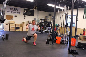 Sara lunges holding dumbbells during the 0630 CrossFit Missoula group WOD.