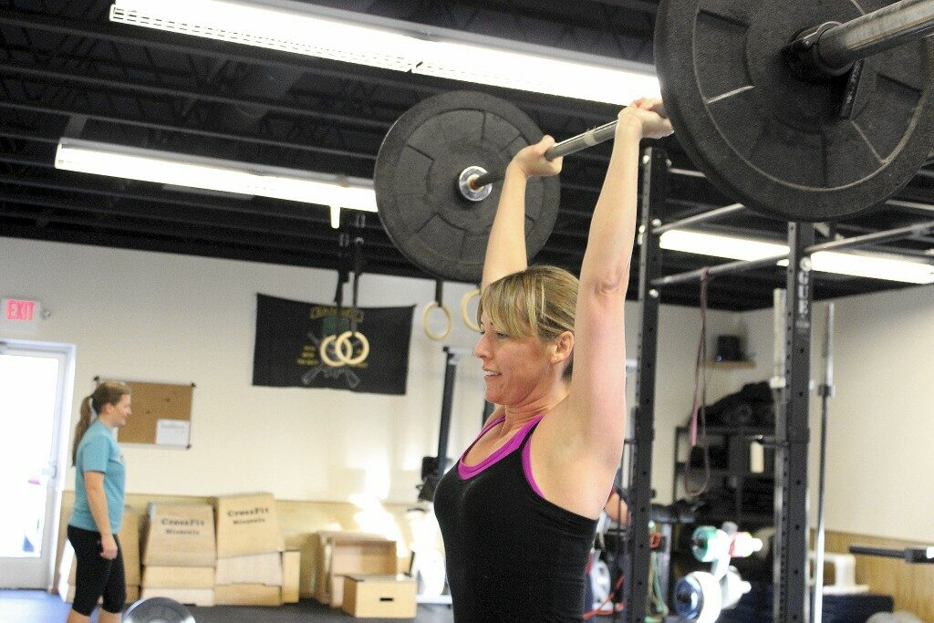 Lisa pressing heavy weight overhead during the 1700 WOD class.
