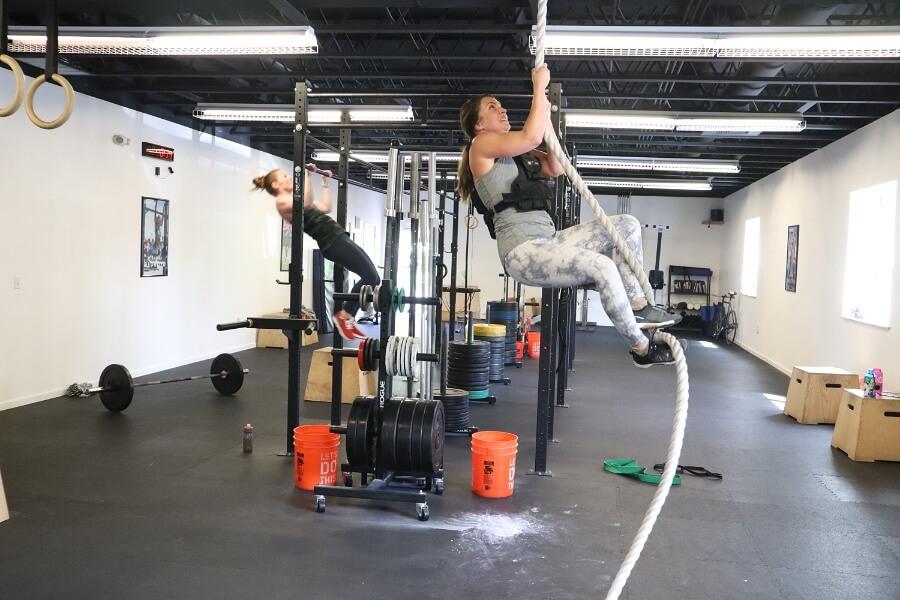 Sara climbing rope while Kate does pull-ups
