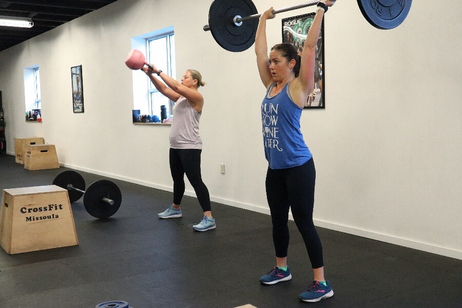 Bridget and April pressing and swinging through the Saturday WOD.